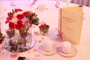 Die Hochzeitsdekoration auf einem Banketttisch mit Blumen, Kerzen und Getränkekarte.