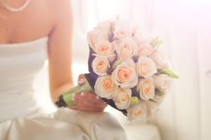 Ein Brautstrauß mit hellen Rosen in der Hand der Braut.