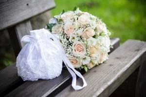 Der Brautstrauß mit hellen Rosen auf einer hölzernen Bank.