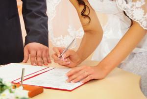 Ein Hochzeitspaar unterzeichnet die Hochzeitsurkunde beim Standesamt.