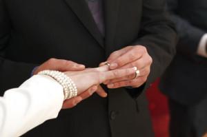 Ein Bräutigam steckt seiner Braut bei der Hochzeit den Ring an den Finger.